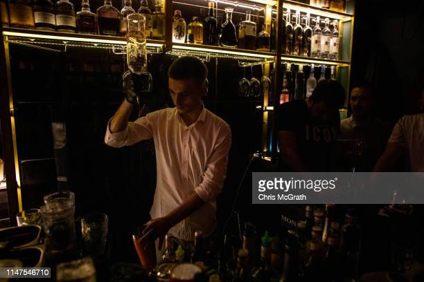 Mixologist makes a cocktail at the upscale bar and nightclub Bon Vivant on May 3, 2019 in Pristina, Kosovo. A recent EU-backed summit failed to...