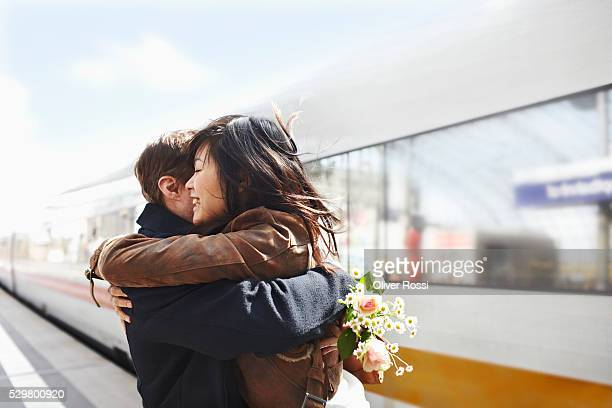 mix-race couple embracing on railway station platform - mid volwassen koppel stockfoto's en -beelden