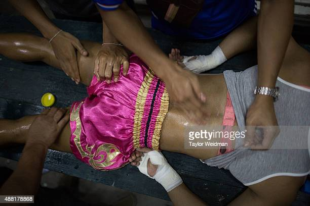 """Mixture of herbal oil and vaseline is applied to Rose's body before a Muay Thai match on September 11, 2015 in Bangkok, Thailand. Somros """"Rose""""..."""