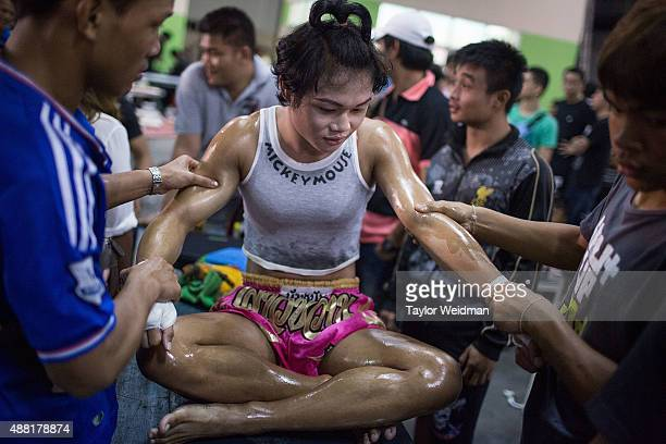 "Mixture of herbal oil and vaseline is applied to Rose's body before a Muay Thai match on September 11, 2015 in Bangkok, Thailand. Somros ""Rose""..."