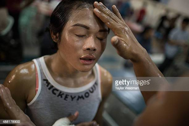 A mixture of herbal oil and vaseline is applied to Rose's body before a Muay Thai match on September 11 2015 in Bangkok Thailand Somros Rose...