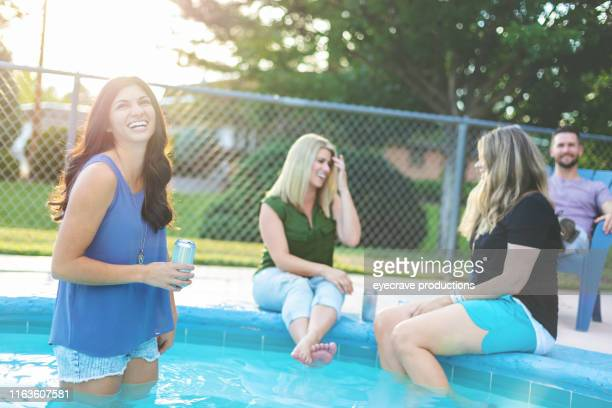 Mixture of Male and Famale Adults enjoying a pool side party in casual clothing