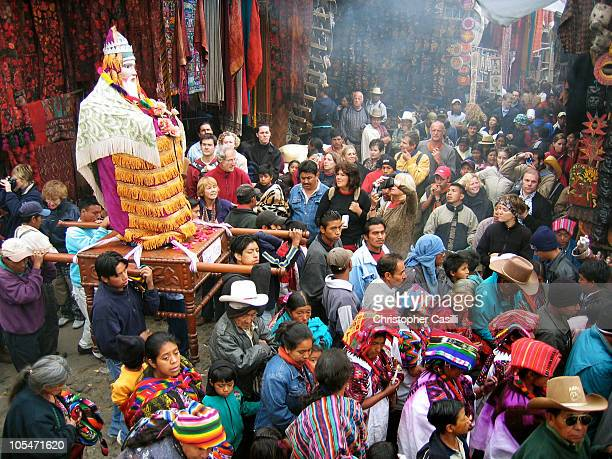 Mixture of Mayan and Christian religious traditions, the main procession of Fiesta de Santo Tomas winds its way though the market area in...