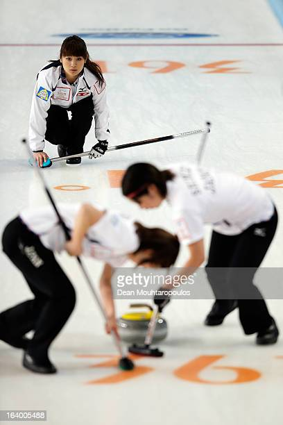 Miyo Ichikawa of Japan throws the stone as Emi Shimizu and Chiaki Matsumura sweep in the match between Japan and Italy on Day 4 of the Titlis Glacier...