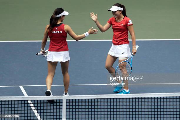 Miyu Kato and Makoto Ninomiya of Japan celebrate a point in their doubles match against Johanna Konta and Heather Watson of Great Britain during day...