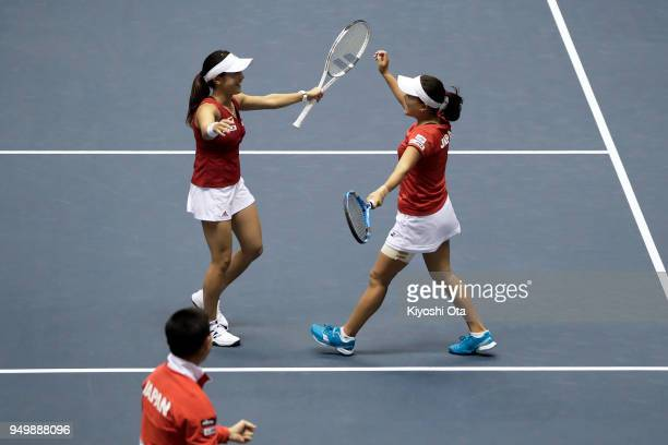 Miyu Kato and Makoto Ninomiya of Japan celebrate as they win their doubles match against Johanna Konta and Heather Watson of Great Britain during day...