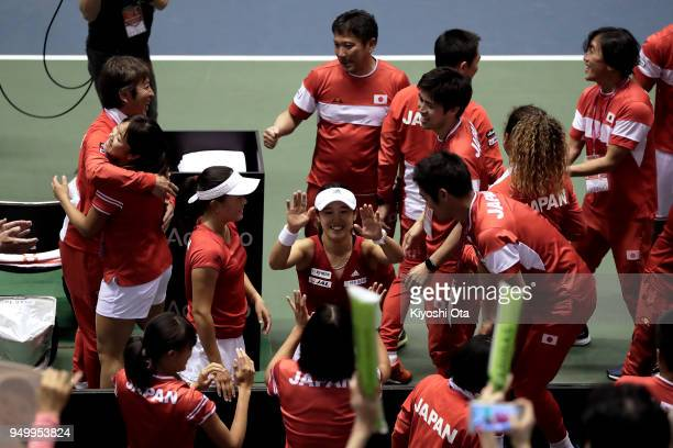 Miyu Kato and Makoto Ninomiya of Japan celebrate the team's 32 victory with other members of the Japan Fed Cup team and team staff after their...