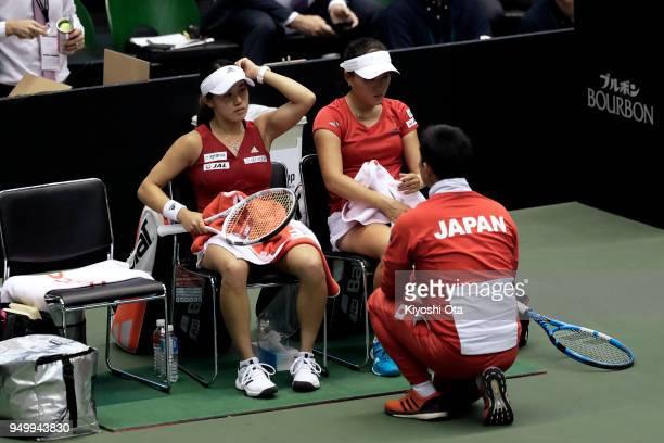 Miyu Kato and Makoto Ninomiya of Japan listen to team captain Toshihisa Tsuchihashi of Japan in their doubles match against Johanna Konta and Heather...