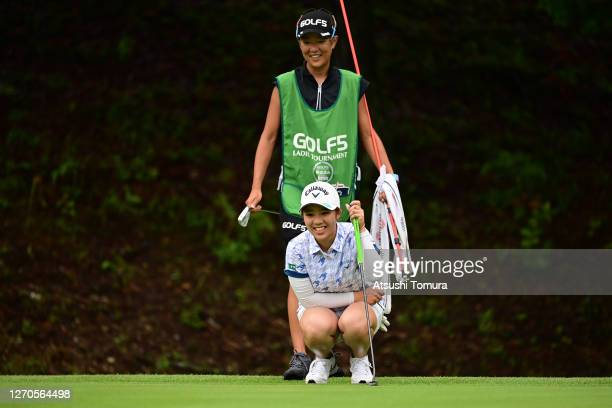 Mizuki Tanaka of Japan lines up a putt with her caddie on the 6th green during the first round of the GOLF5 Ladies Tournament at the GOLF5 Country...