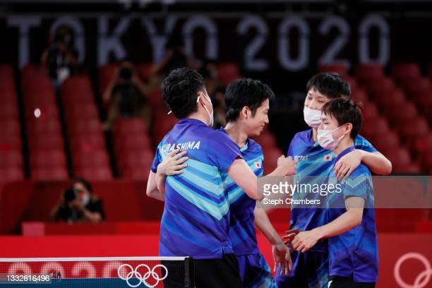 Mizutani Jun of Team Japan is embraced by his teammates Harimoto Tomokazu and Koki Niwa after winning their Men's Team Bronze Medal table tennis...