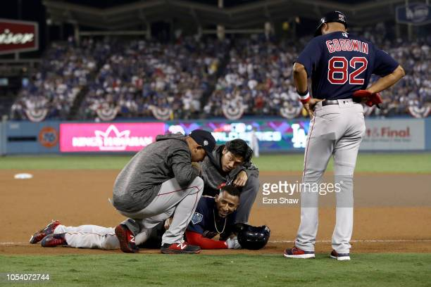Mmanager Alex Cora and first base coach Tom Goodwin look on as Eduardo Nunez of the Boston Red Sox is tended to by the trainer after hitting a single...