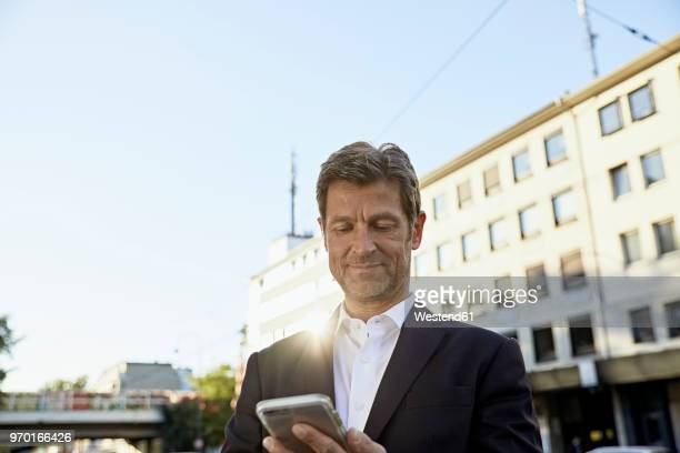 mmature businessman using smartphone in the city - só um homem maduro imagens e fotografias de stock