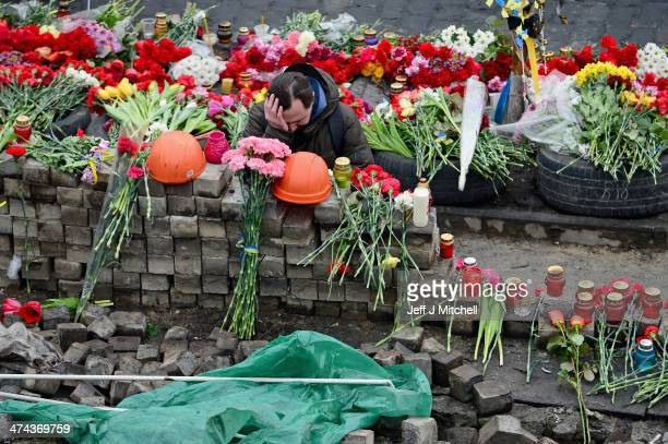 A mna reacts next to flowers left for antigovernment demonstrators killed in clashes with police on February 22 2014 in Kiev UkrainePrime Minister...