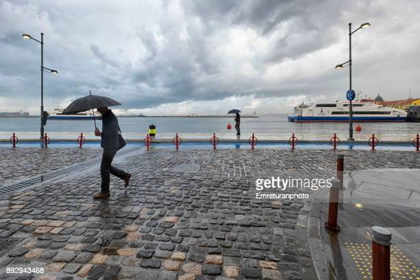 mna walking with umbrella at republic square with ferry at the background in izmir. - emreturanphoto stockfoto's en -beelden