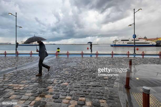 mna walking with umbrella at republic square with ferry at the background in izmir. - emreturanphoto foto e immagini stock