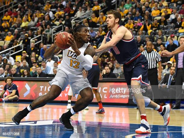 Mo AlieCox of the Virginia Commonwealth Rams drives past TJ Cline of the Richmond Spiders during the semifinals of the Atlantic 10 Basketball...