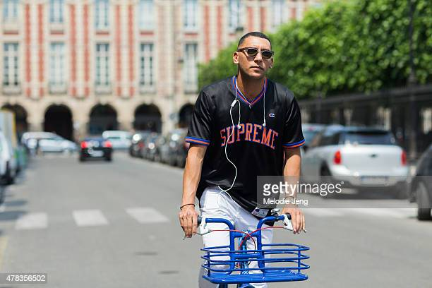Mo Anwar exits the Lemaire show by bike in Marc Jacobs sunglasses Supreme/Champion top JCrew pants and Prada shoes on June 24 2015 in Paris France