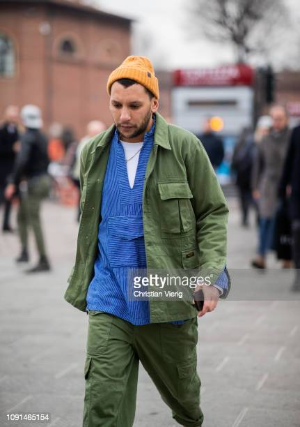Mo Anwar is seen wearing military olive jacket and pants yellow beanie during the 95th Pitti Uomo at Fortezza Da Basso on January 08 2019 in Florence...