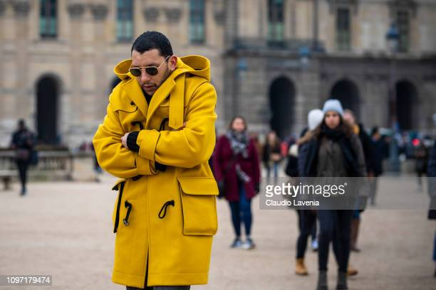 Mo Anwar wearing a yellow coat is seen in the streets of Paris before the Kenzo show on January 20 2019 in Paris France