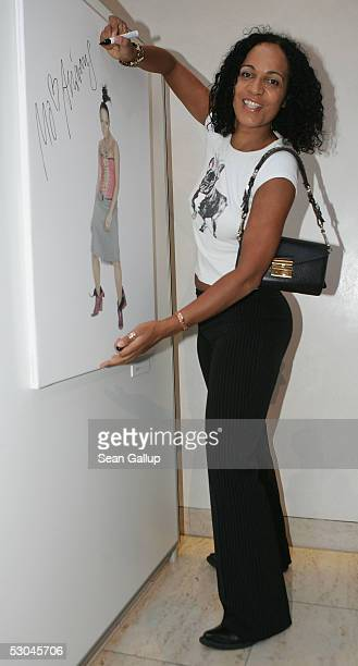 Mo Asumang signs a portrait of herself at the Prominence for Charity Benefit Gala June 9 2005 in Berlin Germany The evening featured photographs of...