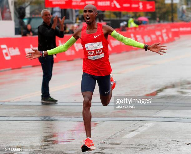 Mo Farah of Britain celebrates as he crosses the finish line to win the Chicago Marathon in Chicago on October 7 as he is applauded by Mayor of...