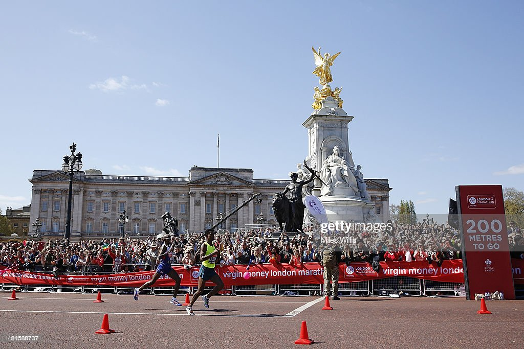 Mo Farah of Great Britain (L) and Feyisa Lilesa of Ethiopia pass Buckingham Palace and the Queen Victoria Memorial during the Virgin London Marathon on April 13, 2014 in London, England.