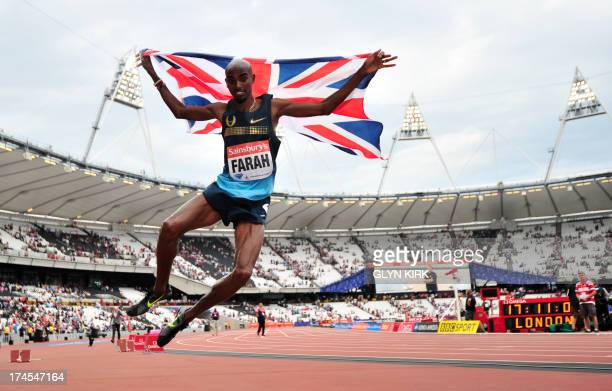 Mo Farah of Great Britain jumps in the air while wrapped in th Union Jack flag after winning in the mens 3000 metres event during the London...