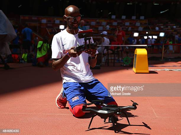 Mo Farah of Great Britain prepares to fly a drone during a practice session ahead of the 15th IAAF World Athletics Championships Beijing 2015 at the...