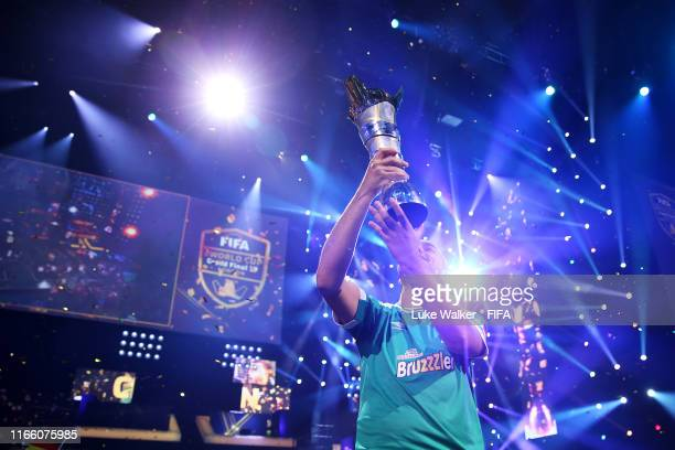Mo Harkous of Germany lifts the trophy following victory in the FIFA eWorld Cup Final against Mosaad Aldossary of Saudi Arabia during Finals day of...