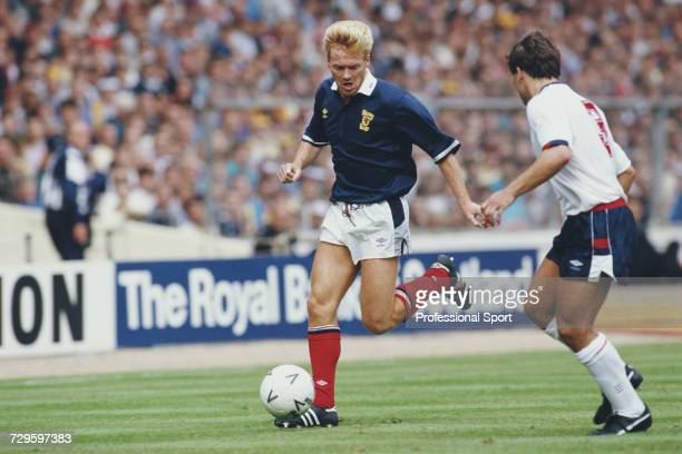 Mo Johnston of Scotland makes a run with the ball as Kenny Sansom of England prepares to make a tackle during the Rous Cup match between England and...