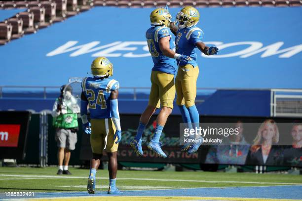 Mo Osling III of the UCLA Bruins celebrates breaking up the pass with Bo Calvert and Qwuantrezz Knight of the UCLA Bruins during the fourth quarter...