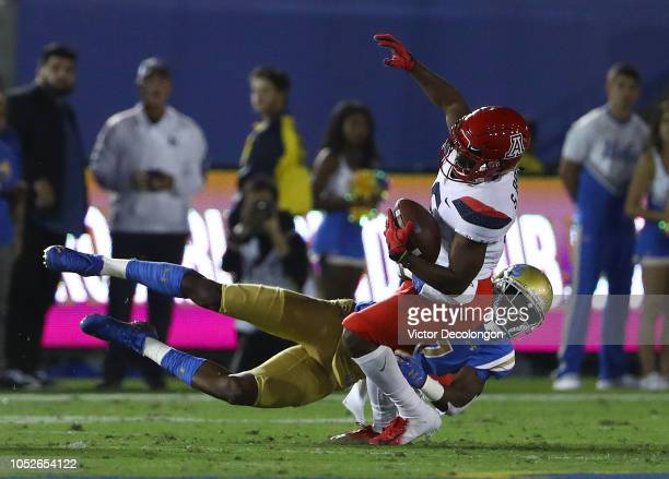 Mo Osling III of the UCLA Bruins tackles Shun Brown of the Arizona Wildcats during the first half of the NCAA college football game at the Rose Bowl...