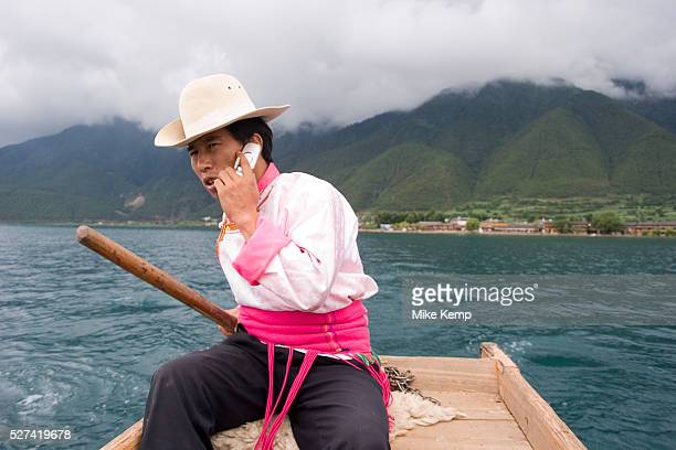 Mo Suo minority man in traditional dress takes a call on his cell phone whilst rowing tourists to a nearby island on Lugu Lake in Yunnan province Mo...