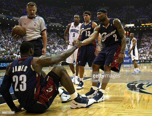 Mo Williams of the Cleveland Cavaliers helps up teammate LeBron James after a foul in the first quarter against the Orlando Magic in Game Six of the...