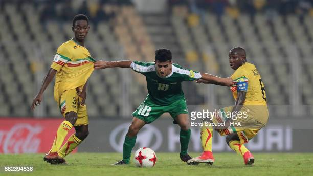 Moamel Kareem of Iraq is challenged by Djemoussa Traore of Mali and Mohamed Camara of Mali during the FIFA U17 World Cup India 2017 Round of 16 match...