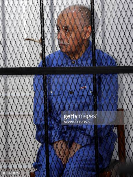 Moamer Kadhafi's last premier AlBaghdadi alMahmudi dressed in prison blues sits behind the accused cell during his trial in a courthouse in Tripoli...