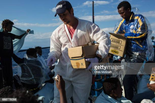Moas crewmember distrubutes food to refugees and migrants on board the Migrant Offshore Aid Station 'Phoenix' vessel on May 26 2017 off Crotone Italy...