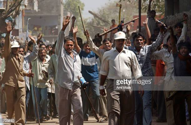 A mob of Hindus wielding swords and sticks back off after Indian Rapid Reaction Force officers stopped them from attacking a small group of Muslims...