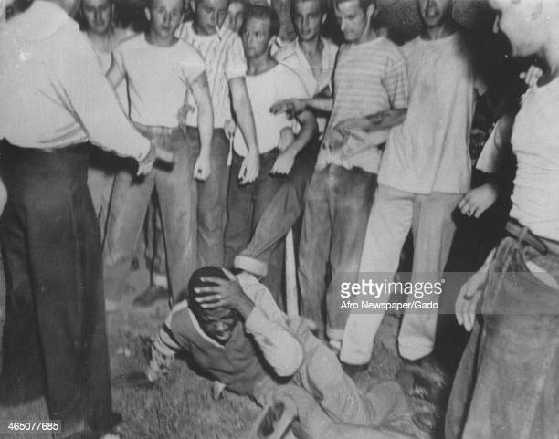 A mob of white teenagers kicks and beats an African American man who holds his head and screams in pain during a lynching 1950
