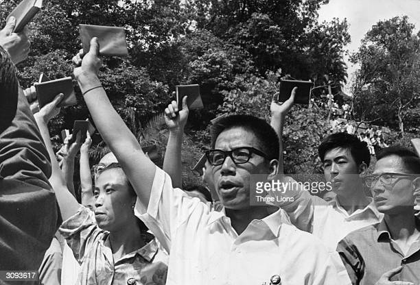 A mob outside Government House in China shouts communist slogans and waves copies of Mao TseTung's 'little red book' entitled 'The Thoughts of...