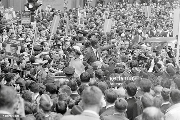Surrounded by a surging throng of New Yorkers Sen John F Kennedy and his wife Jacqueline try to greet admirers in all directions here at once The...
