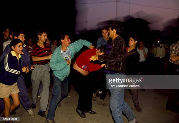 A mob surround a government supporter as he is attacked by an antiGovernment crowds in Bucharest Romania Months of unrest around University Square...