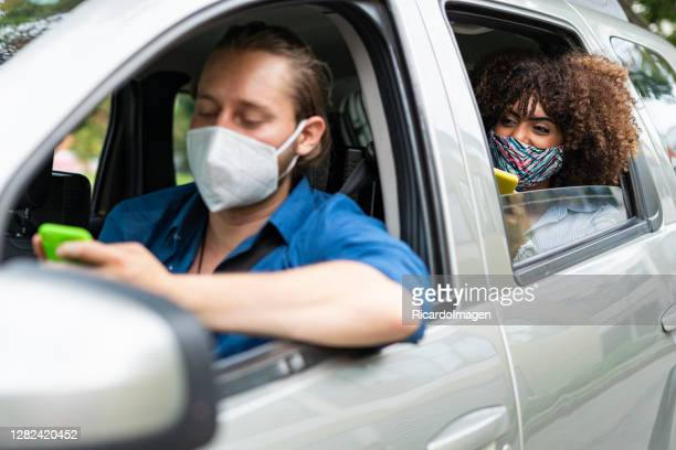 mobile application driver taking a passenger to their destination is wearing face masks to prevent covid-19 - world sports championship stock pictures, royalty-free photos & images