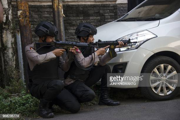 Mobile brigade police take position as they patrol outside the Surabaya police headquarters following a suicide attack in Surabaya on May 14 2018 Two...