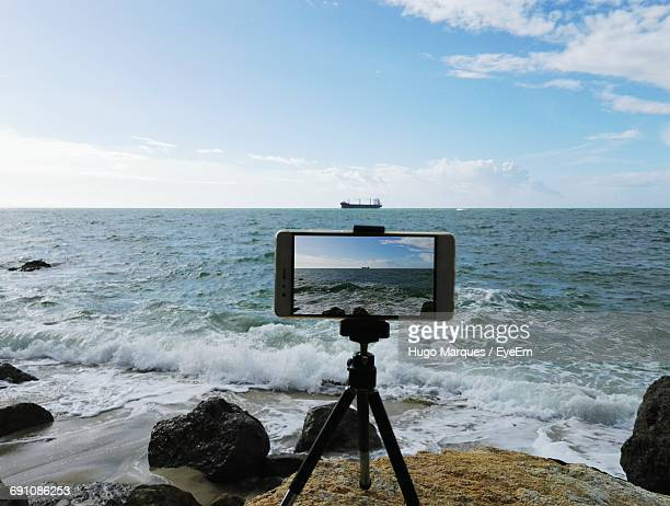 mobile camera with tripod at sea shore against sky - tripod stock pictures, royalty-free photos & images