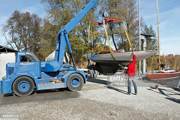 Mobile crane lifting a sail boat Chiemgau Upper Bavaria Germany