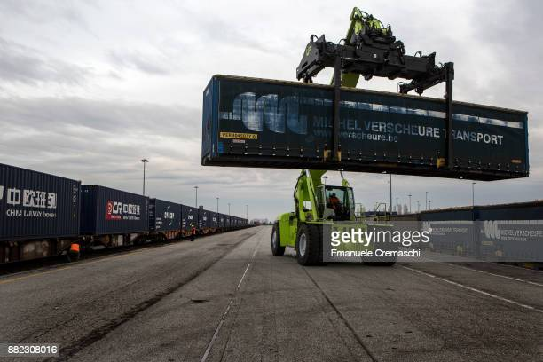 A mobile crane stacks containers past the first freight train to run from Italy to China hauling 22 containers moments before its departure on...