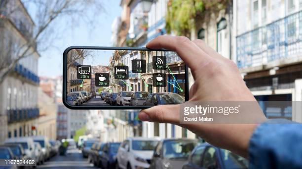 mobile device with augmented reality showing useful tourist information in a city street. - erweiterte realität stock-fotos und bilder