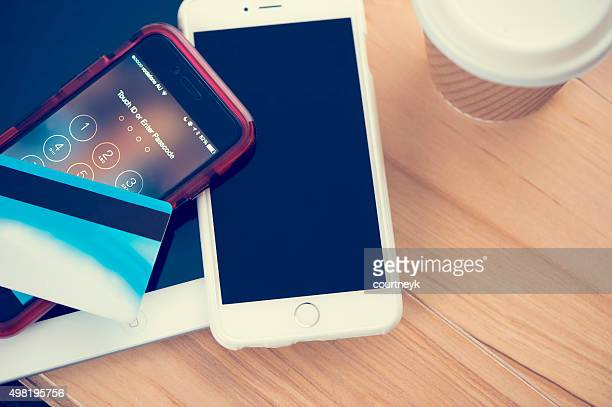 mobile devices with credit card on table with coffee. - apple credit card stock pictures, royalty-free photos & images