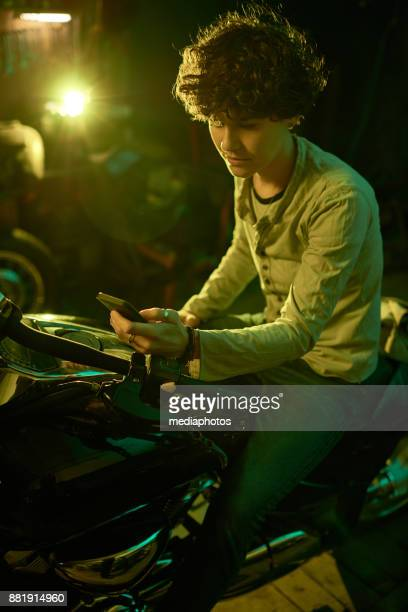 Mobile female mechanic in dark workshop